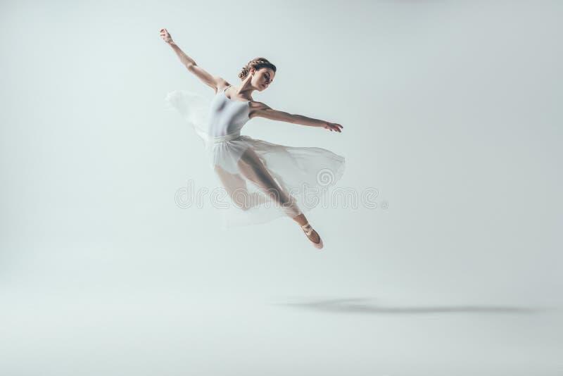 elegante balletdanser die in witte kleding in studio springen stock foto