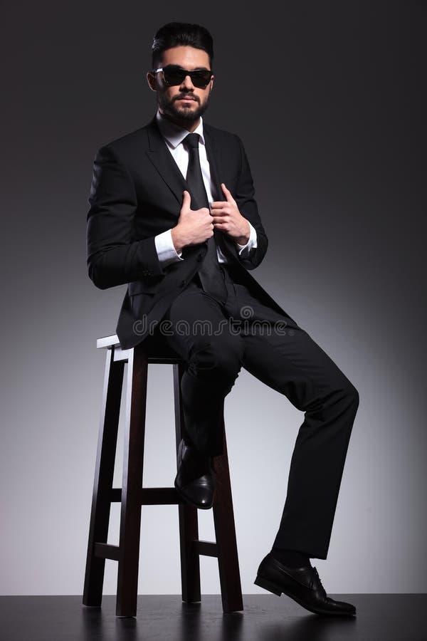 Elegante bedrijfsmens die zwarte zonnebril dragen die zijn jasje bevestigen royalty-vrije stock foto's