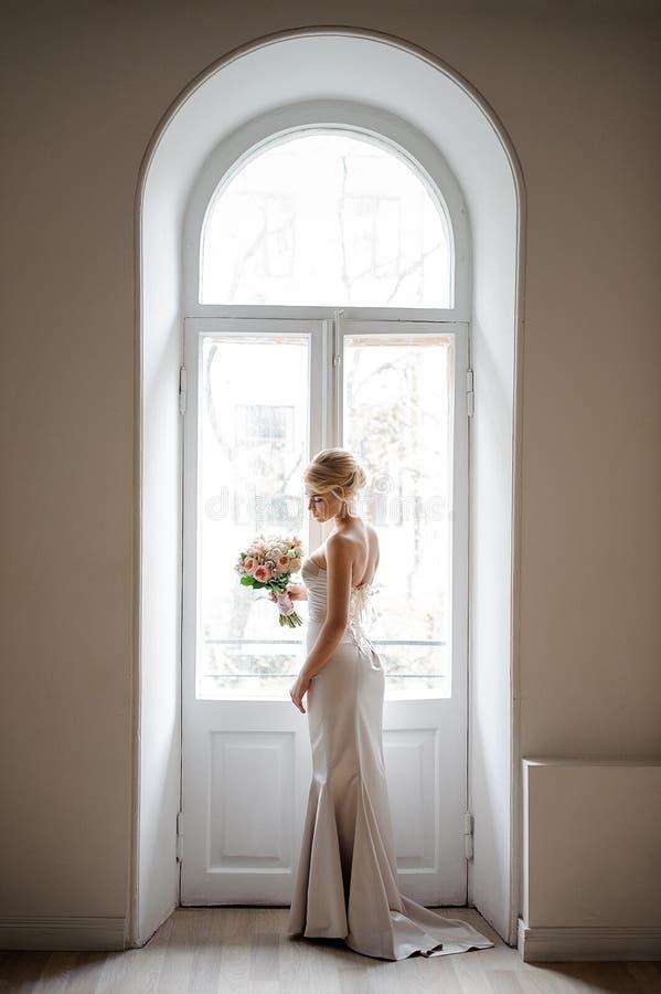 Elegante blonde Braut in einem reizenden weißen Kleid, das einen Hochzeitsblumenstrauß hält lizenzfreies stockbild
