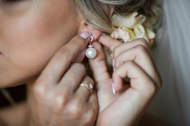 Elegante blondebruid die op oorringenclose-up zetten, die voorbereidingen treffen voor stock fotografie