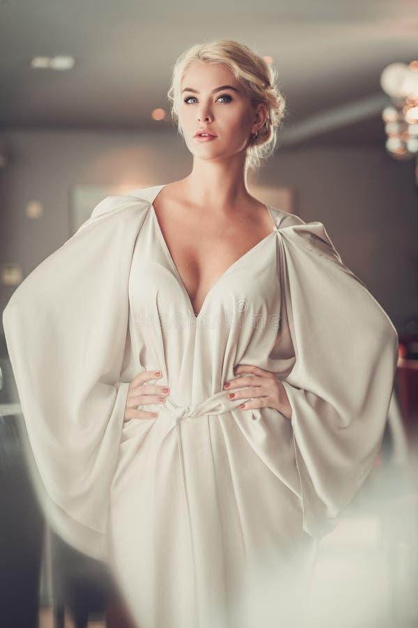 Elegante blondedame in beige avondjurk in restaurant royalty-vrije stock afbeeldingen