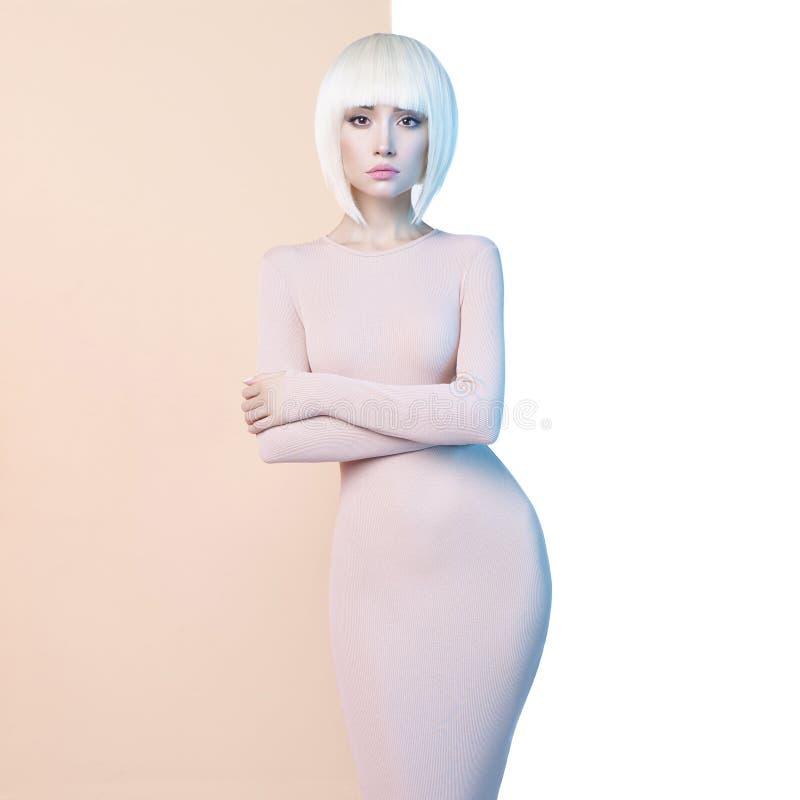 Elegante Blondine im geometrischen beige und weißen Hintergrund stockbilder