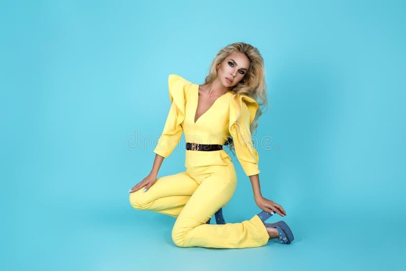 Elegante Blondine im stilvollen gelben Overall und in den modernen Zusätzen auf Farbhintergrund Sch?nes Mode-Modell auf Blau stockfoto