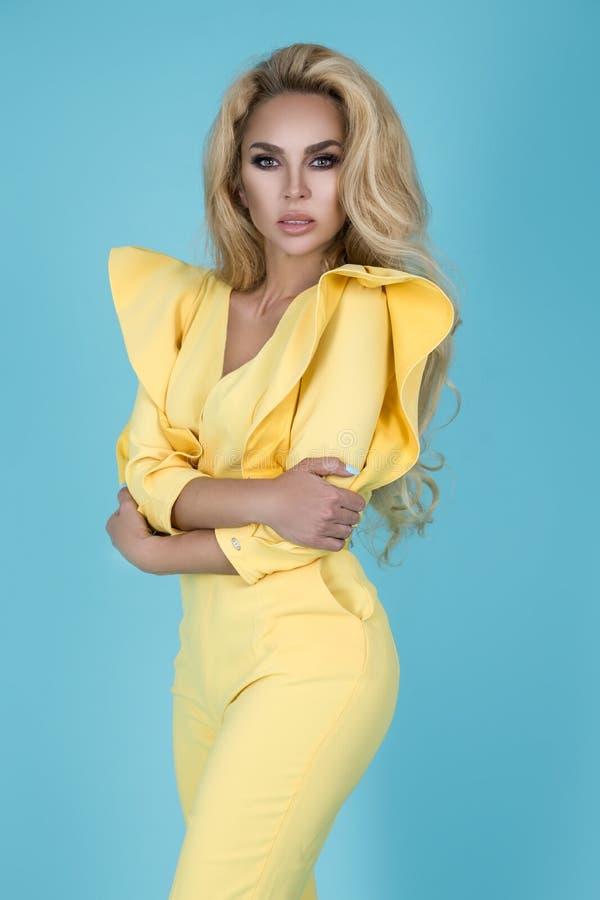 Elegante Blondine im stilvollen gelben Overall und in den modernen Zusätzen auf Farbhintergrund Sch?nes Mode-Modell auf Blau stockbild