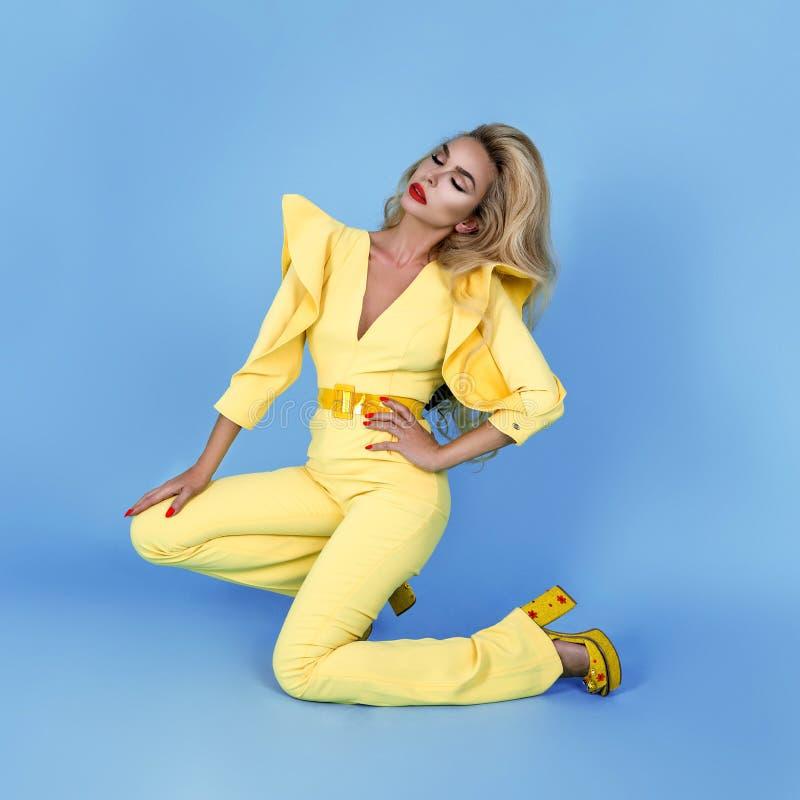 Elegante Blondine im stilvollen gelben Overall und in den modernen Zusätzen auf Farbhintergrund Sch?nes Mode-Modell auf Blau lizenzfreies stockbild
