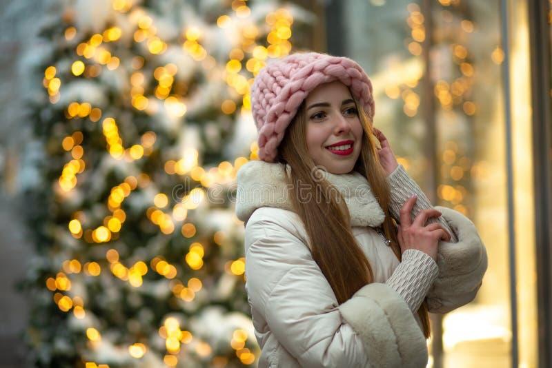 Elegante Blondine mit den roten Lippen, die volumetrischen Hut und Wintermantel gehend hinunter die Straße verziert mit Girlanden lizenzfreie stockbilder