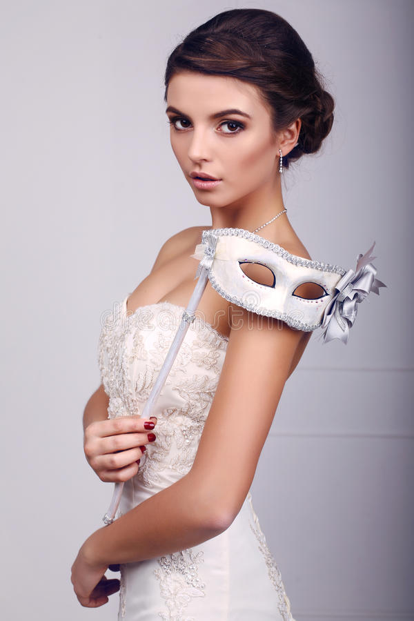 Elegante Braut im Hochzeitskleid mit Maske in ihren Händen stockbilder