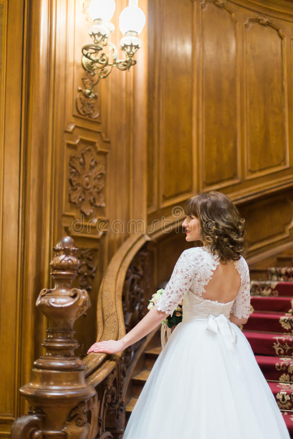 Elegante Braut mit dem Blumenstrauß, der Hand auf Handlauf am alten Weinlesehaus hält lizenzfreies stockfoto