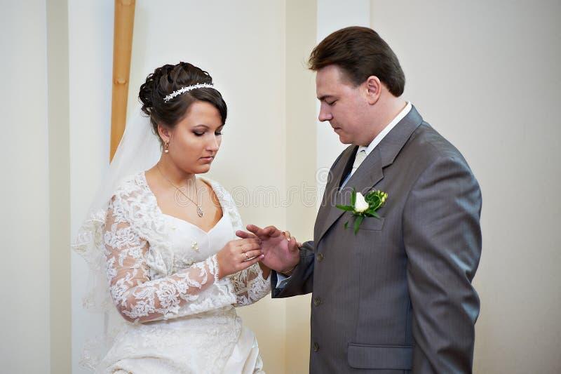Elegante Braut trägt einen Hochzeitsring ein glücklicher Bräutigam stockbilder
