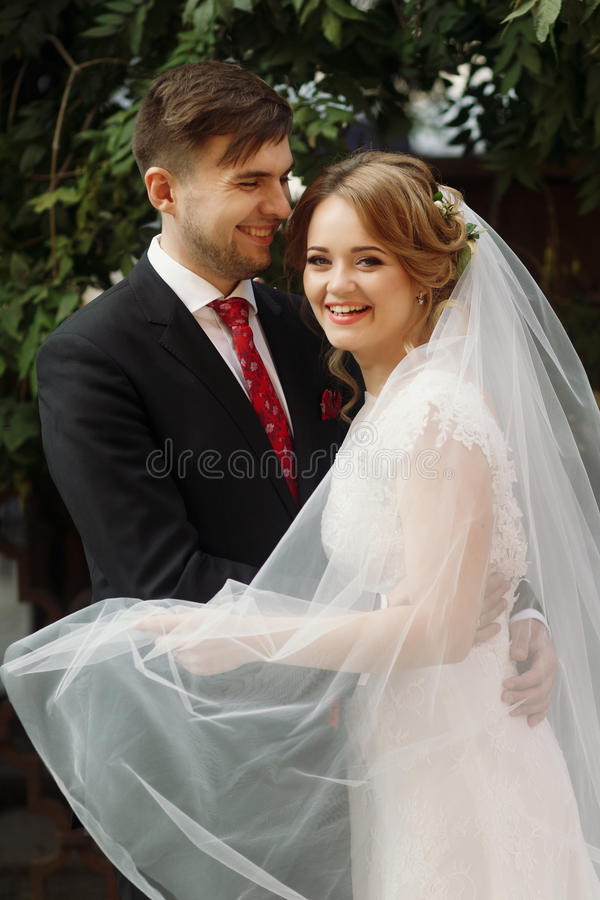 Elegante bruid en bruidegom die in Europese stadsstraat bij eveni glimlachen royalty-vrije stock afbeeldingen