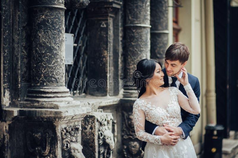 Elegante bruid met bruidegom die dichtbij oude katholieke kathedraal lopen royalty-vrije stock foto's
