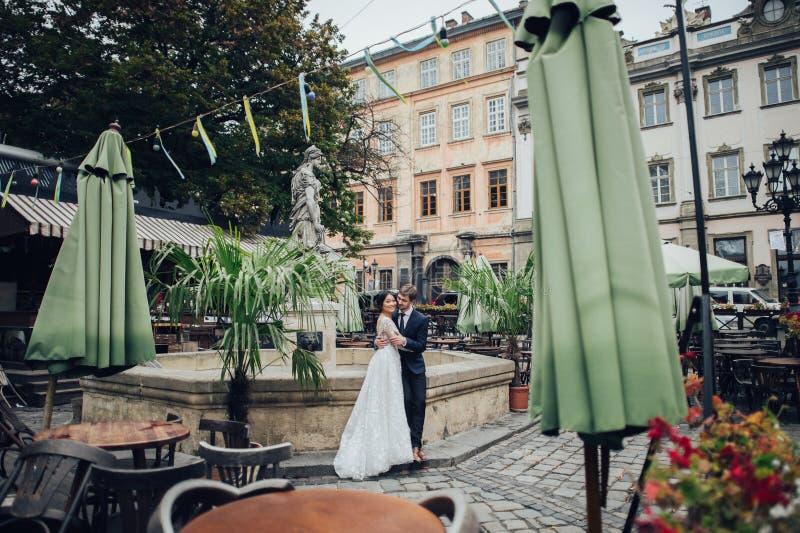 Elegante bruid met bruidegom die dichtbij oude katholieke kathedraal lopen stock foto's