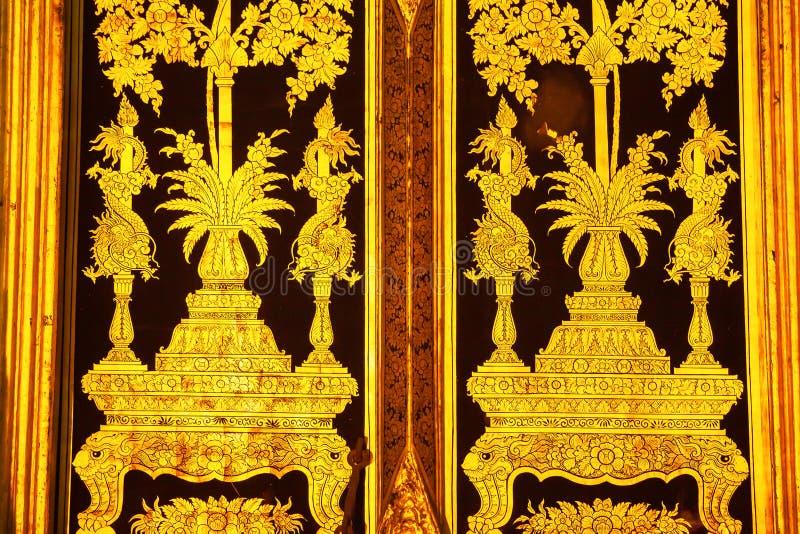 Elegante da pintura dourada da arte tailandesa tradicional do estilo na porta antiga fotos de stock