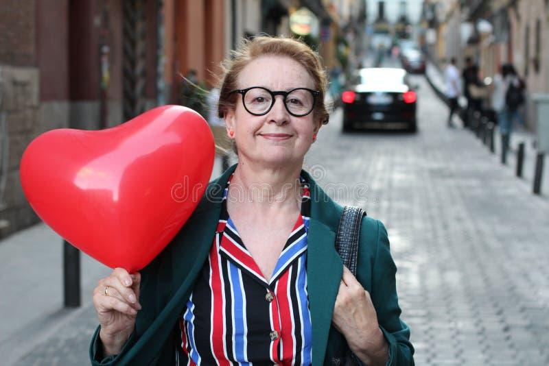 Elegante dame die hart gevormde ballon tonen stock fotografie