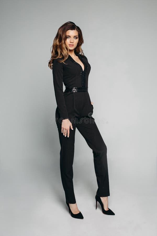 Elegante Dame im schwarzen schimmernden Gesamten und in den hohen Absätzen stockfotos