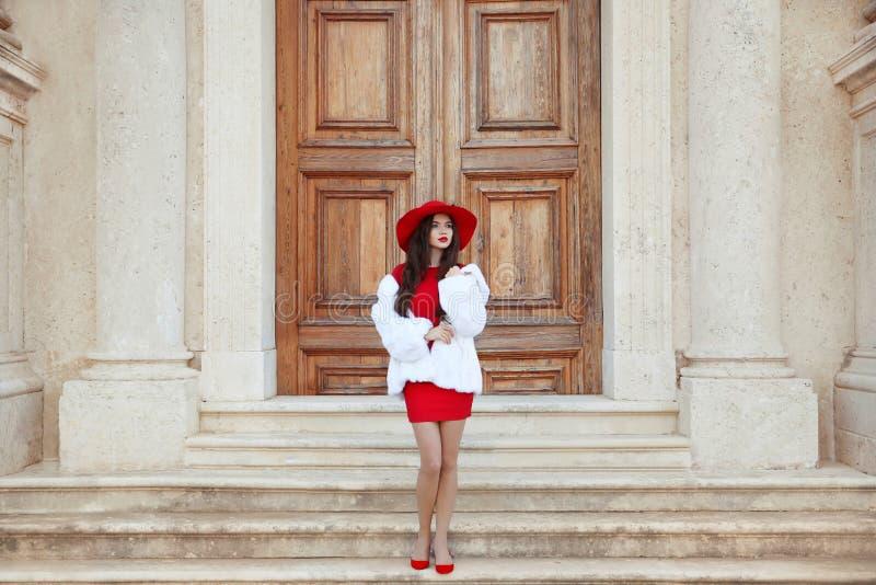 Elegante Dame Maniervrouw in rode hoed en kleding die in whit dragen stock foto's