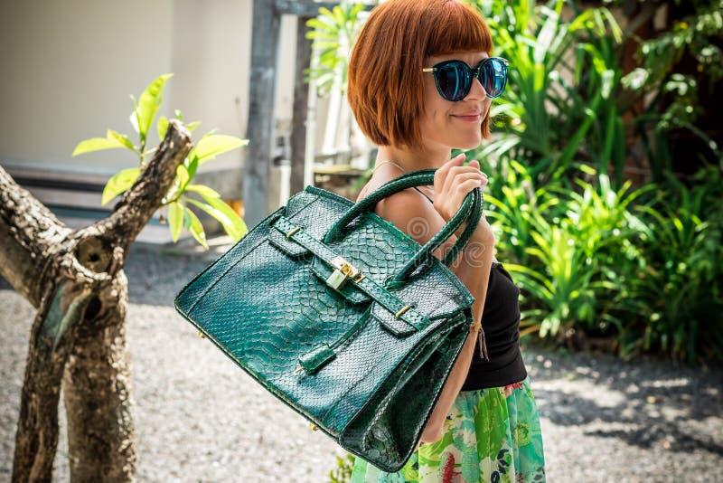 Elegante dame met modieus kort kapsel en glazen die een zak van de de huidpython van de luxeslang houden Het eiland van Bali stock afbeelding