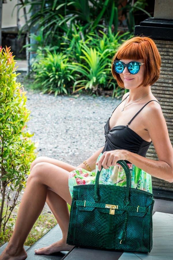 Elegante dame met modieus kort kapsel en glazen die een zak van de de huidpython van de luxeslang houden Het eiland van Bali royalty-vrije stock foto's
