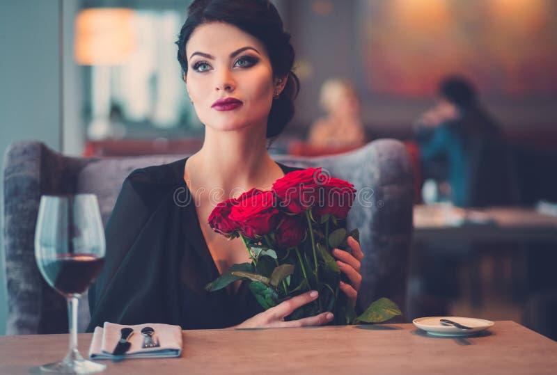 Elegante Dame mit roten Rosen im Restaurant stockfotografie