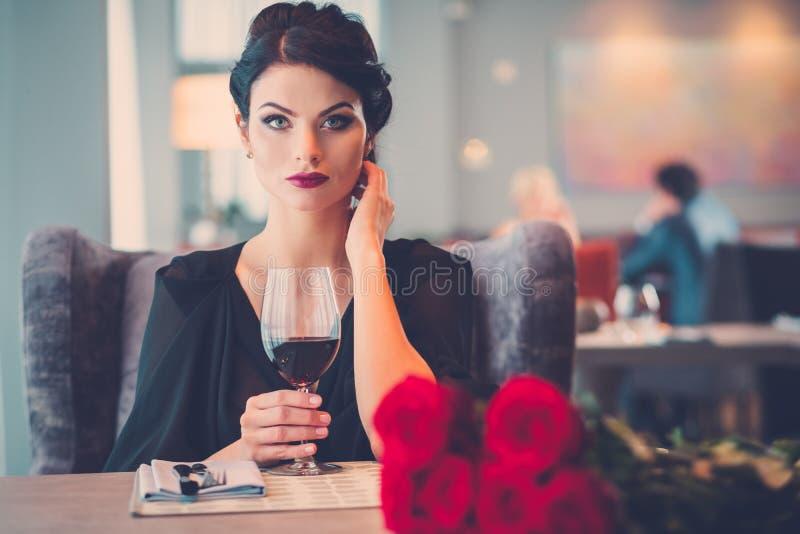 Elegante Dame mit roten Rosen im Restaurant lizenzfreie stockfotografie