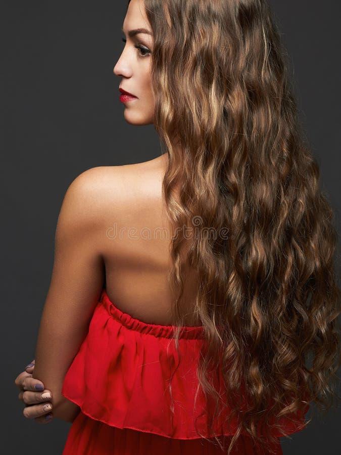 Elegante dame in rode kleding Vrouwelijke rug stock foto