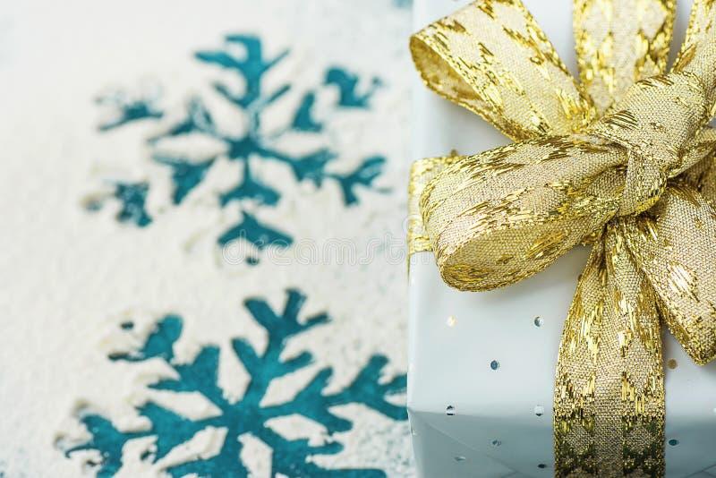 Elegante die Giftdoos in Grey Silver Paper met Polka Dots Golden Ribbon op Sneeuwachtergrond met Blauwe Sneeuwvlokken wordt verpa stock afbeelding