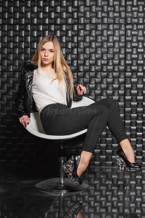 Elegante Frau, die auf einem Stuhl aufwirft stockbild