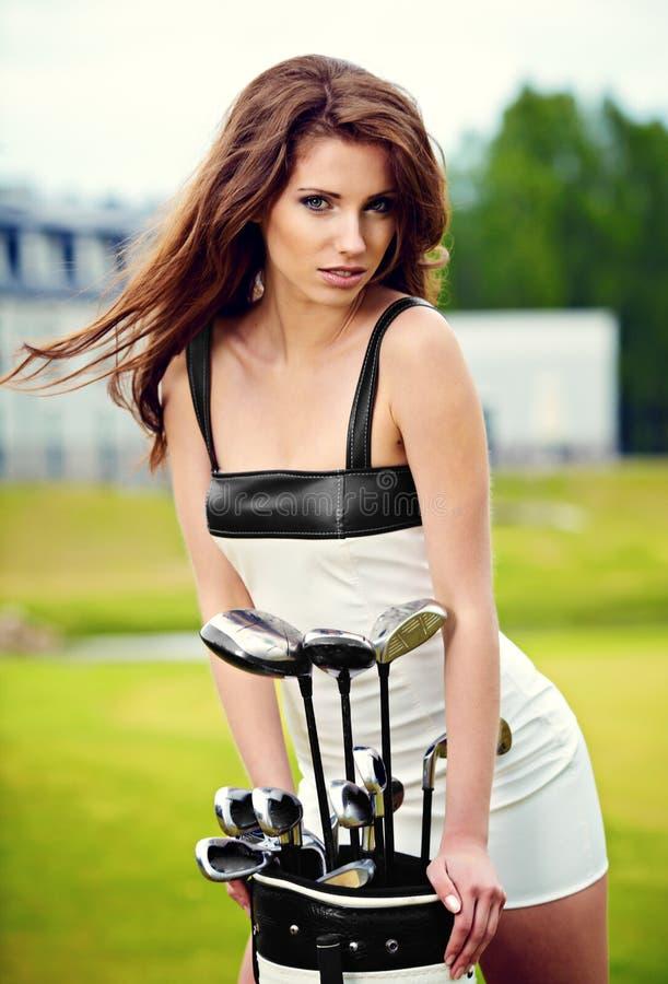 Elegante Frau, die Golf spielt stockbilder