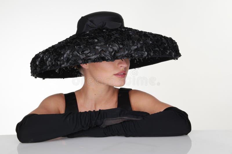 Elegante Frau, die schwarzen Hut und Handschuhe trägt stockfotografie