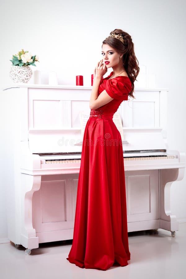 Elegante Frau In Einem Langen Roten Kleid Steht Am Klavier In A ...