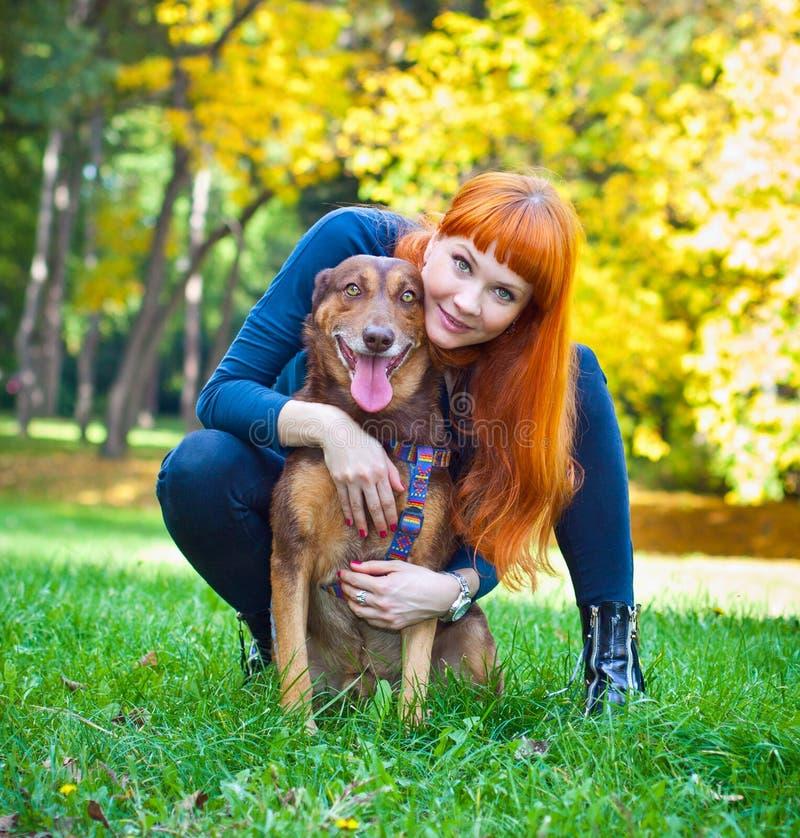 Elegante Frau hat Spaß mit ihrem großen Hund im Park stockfoto
