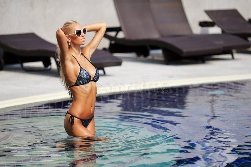 Elegante Frau im Bikini mit dem gebräunten dünnen Körper, der nahe einem Schwimmen aufwirft lizenzfreies stockbild