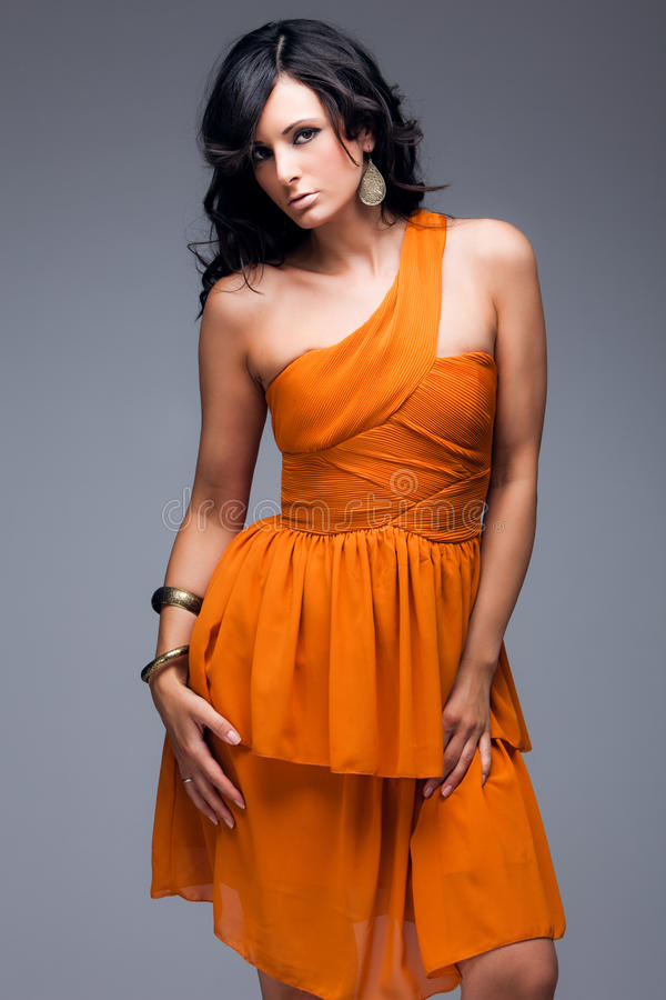 Elegante Frau im orange Kleid stockfoto