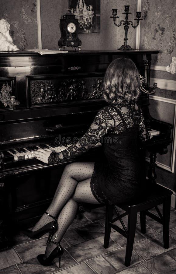 Elegante Frau im schwarzen Kleid, welches das Klavier spielt Schöne weibliche Beine in den Strümpfen und in den Fersen lizenzfreie stockfotos