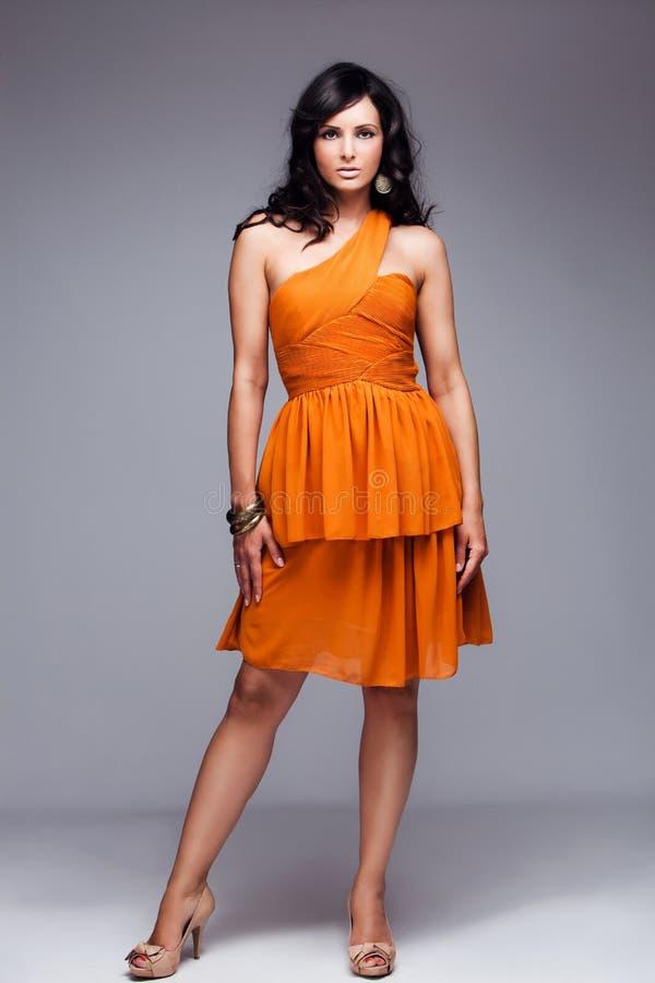 Elegante Frau im vollen Karosserienschuß des orange Kleides stockfoto