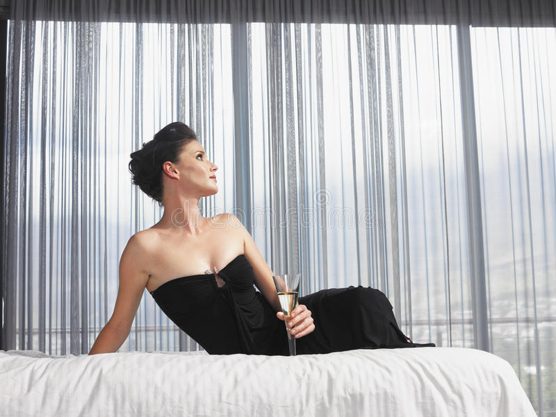 Elegante Frau mit Champagne Glass Sitting In Bed lizenzfreie stockfotos