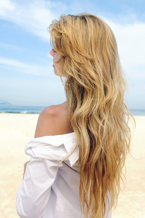Elegante Frau mit dem langen blonden Haar am Strand lizenzfreie stockfotografie