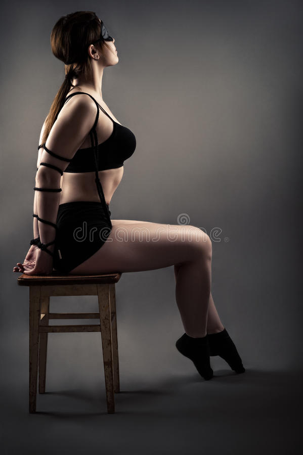 Elegante Frau mit den gebundenen Händen, die auf Stuhl mit geschlossenen Augen sitzen lizenzfreie stockbilder