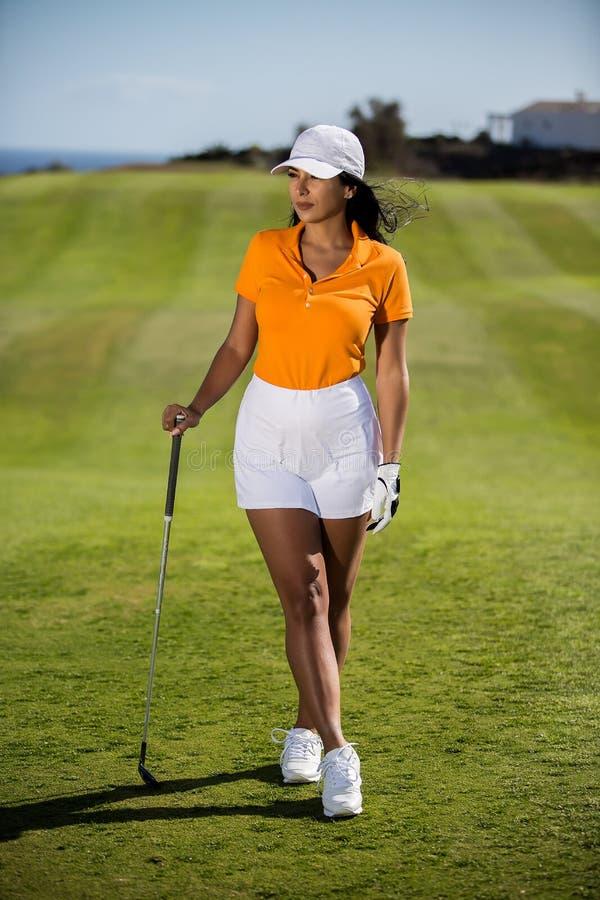 Elegante Frau mit Golffahrer auf Feld stockbild