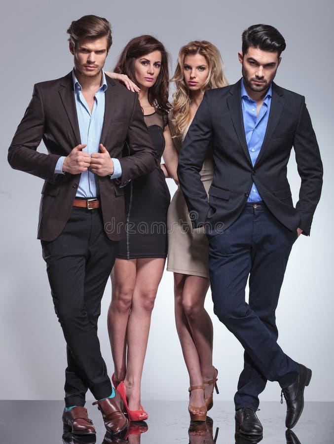 Elegante Frauen, die hinter ihren Männern stehen lizenzfreie stockfotos