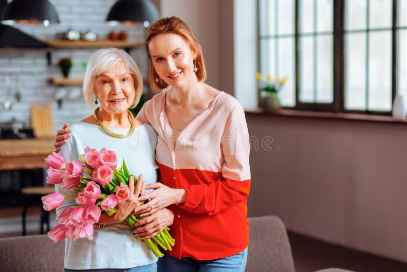 Elegante Freifrau mit den rosa Tulpen, die von der schönen Schwiegertochter gestreichelt werden lizenzfreie stockfotografie