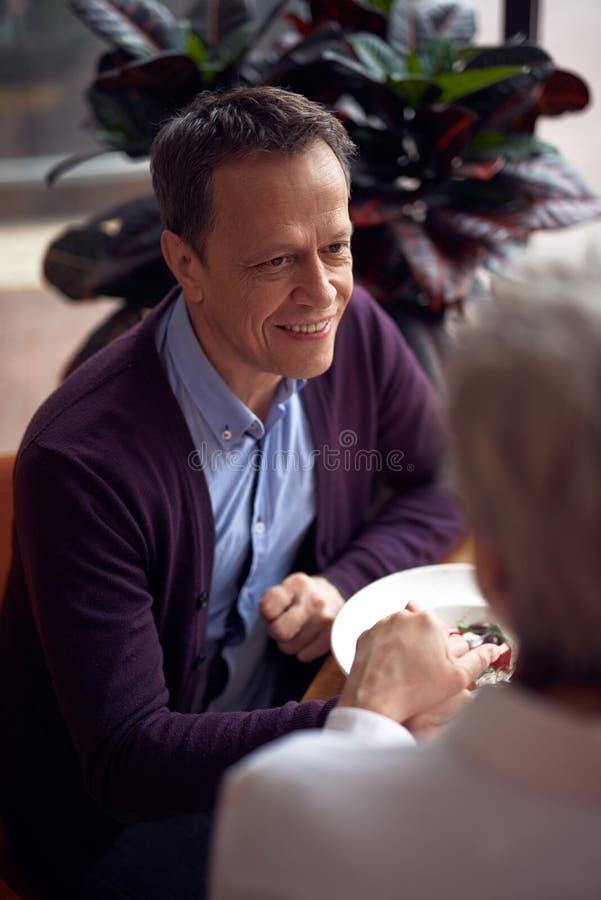 Elegante gealterte Mannholdinghand von Dame im Café lizenzfreies stockfoto