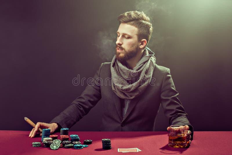 Elegante gebaarde pookspeler bij lijst met whisky en sigaar royalty-vrije stock fotografie