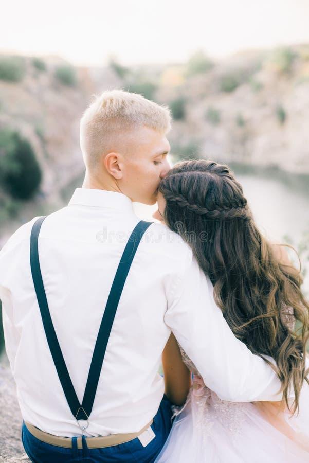 Elegante gelockte Braut und Bräutigam draußen auf dem Hintergrund der See stockfotografie
