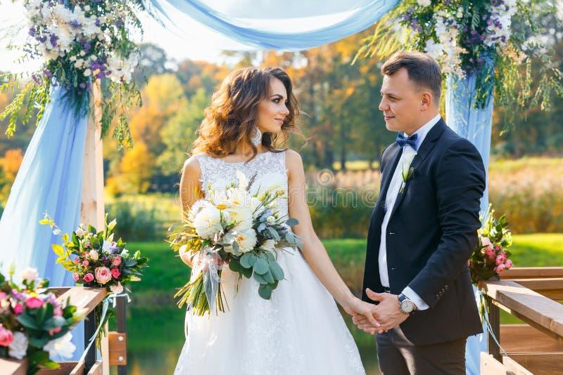 Elegante gelockte Braut und glücklicher Bräutigam lizenzfreie stockbilder