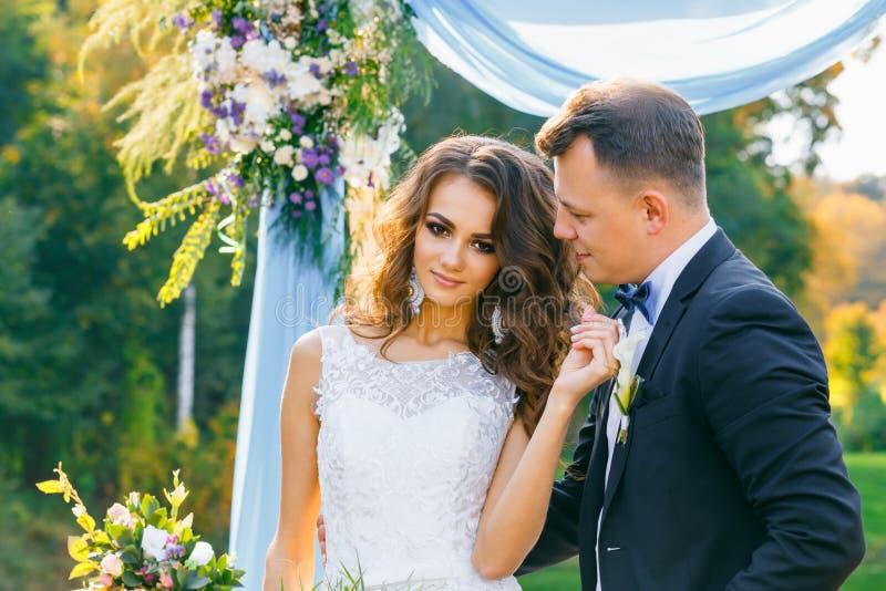 Elegante gelockte Braut und glücklicher Bräutigam stockbild