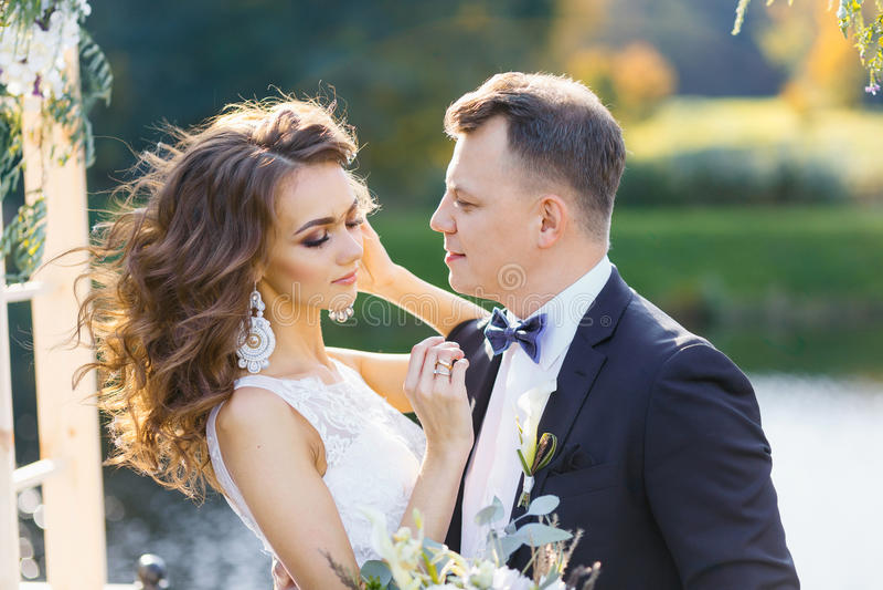 Elegante gelockte Braut und glücklicher Bräutigam draußen auf dem Hintergrund der See stockbilder