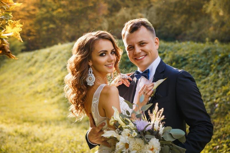 Elegante gelockte Braut und stilvoller Bräutigam stockfoto