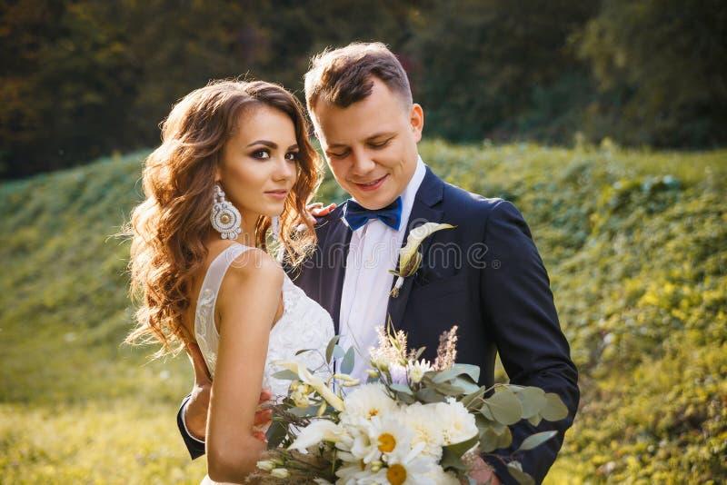 Elegante gelockte Braut und stilvoller Bräutigam lizenzfreies stockfoto