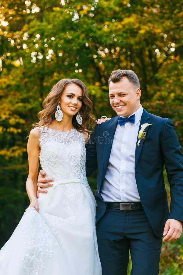 Elegante gelockte Braut und stilvoller Bräutigam lizenzfreie stockfotografie